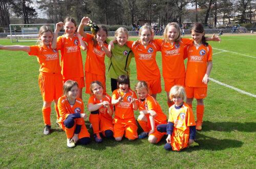 Ein Gruppenfoto mit Mädchen in orangenen Fußballtrikots.
