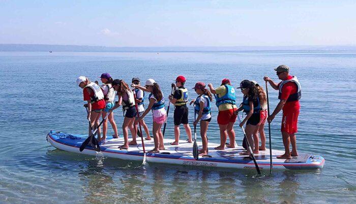 Eine Gruppe von Jugendlichen auf einem Stand Up Paddling-Board.