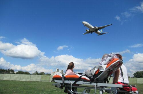 Eine auf einer Krankenliege liegende Person und zwei danebenstehende Menschen, die ein Flugzeug im Himmel anschauen.