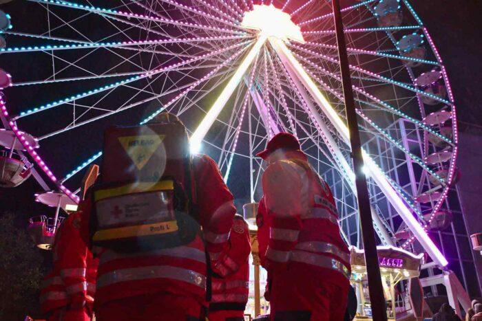 Zwei Rettungshelfer stehen vor einem bunten Riesenrad.