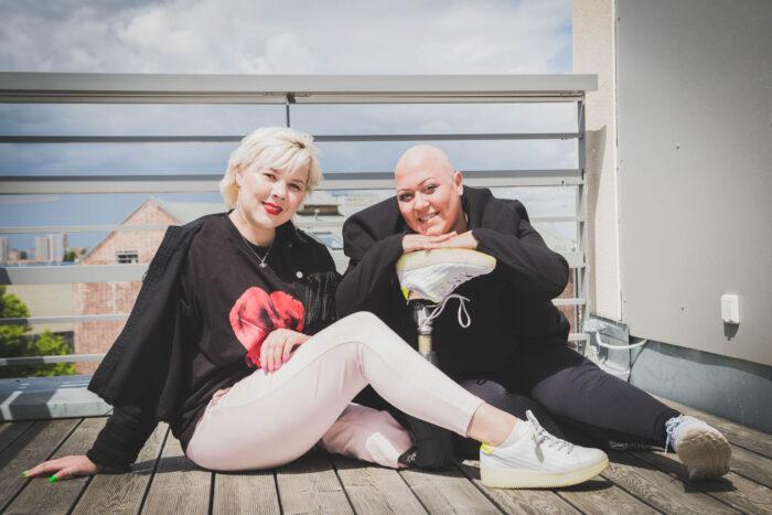 Zwei lächelnde Frauen sitzen auf dem Boden eines Balkons. Eine der Frauen hat einen kahlen Kopf. Der anderen wurde das beim Bein amputiert.