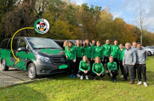 Ein Gruppenfoto mit Fußballspielerinnen in grünen Jacken. Daneben steht ein kleiner Bus.