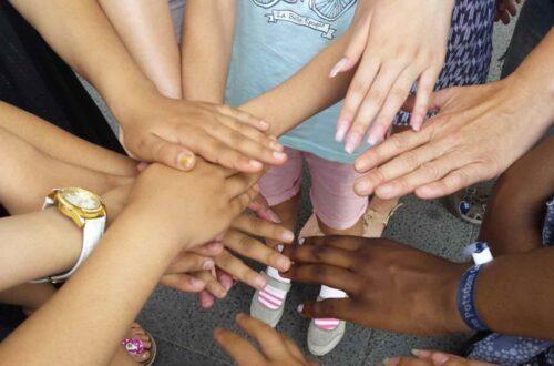 Mehrere Hände, die in einem Kreis von Kindern übereinander gehalten werden.