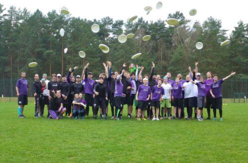 Ein Gruppenfoto mit Menschen in lila Trikots, die Frisbeescheiben hochwerfen.