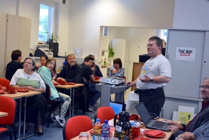 Ein Mann hält einen Vortrag vor Publikum.