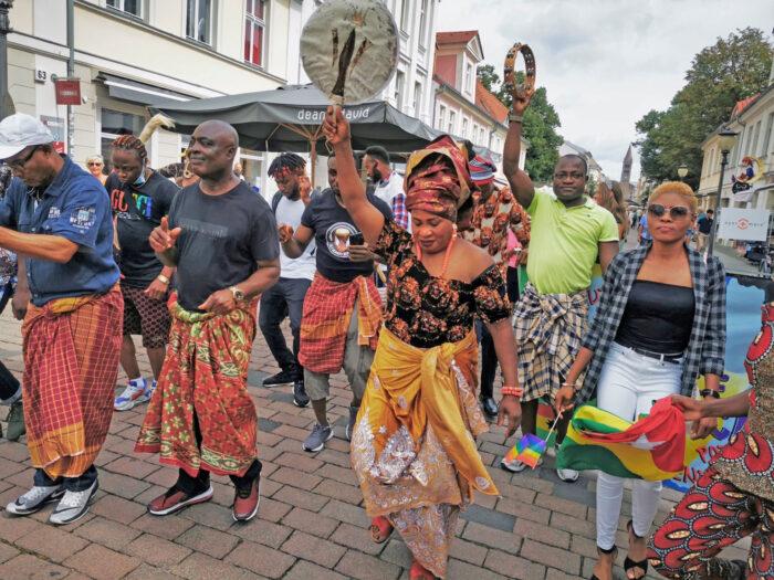 Eine Gruppe afrikanischer oder aus Afrika stammender Menschen mit Musikinstrumenten auf einem Straßenfestival.