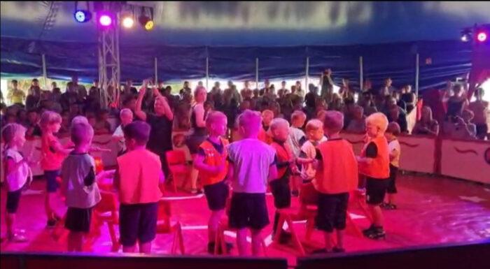 Eine Menge kleiner Kinder in roten Westen stehen vor und hinter Holzstühlen.