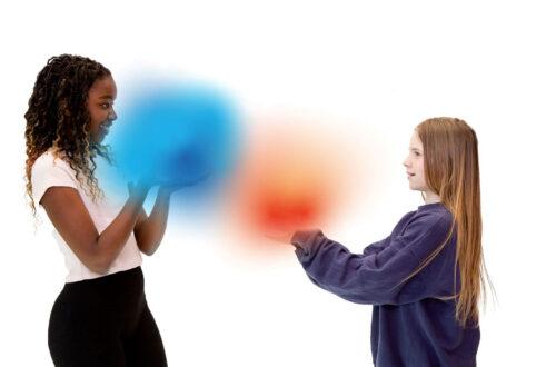Zwei Mädchen, die so aussehen, als ob sie Farbkugeln in den Händen handeln.
