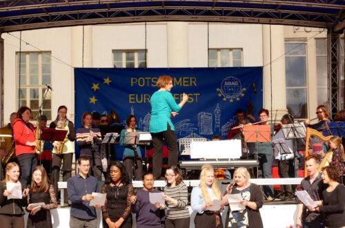 Eine Orchesteraufführung mit Chorsängern im Vordergrund.