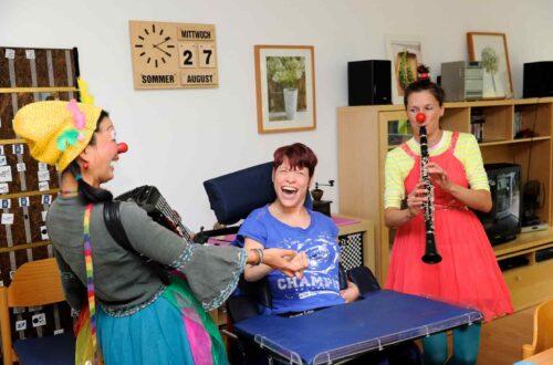 Zwei als Clown verkleidete Frauen mit einer Frau, die im Rollstuhl sitzt.