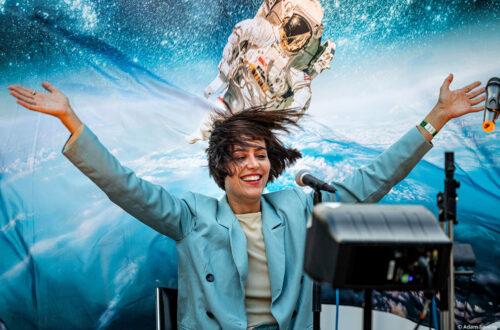 Eine Frau, die gerade etwas aufführt, vor einem Plakat, auf dem ein Astronaut zu sehen ist.