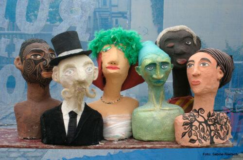 Eine Sammlung von sechs Skulpturen in Form von menschenlichen Oberkörpern in unterschiedlichen Farben.