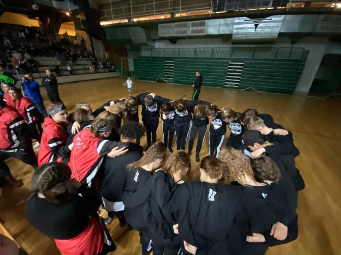 Ein Gruppenfoto von Jugendlichen in Sportkleidung, die im Kreis zusammenstehen.