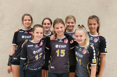 Ein Gruppenfoto junge Mädchen, die Sporttrikots anhaben.