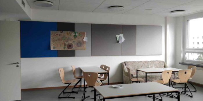 Ein karger Raum mit einem Sofa und ein paar Tischen und Stühlen.
