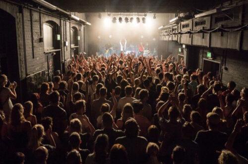 Eine gefüllter Konzertsaal mit einer Band auf der Bühne.