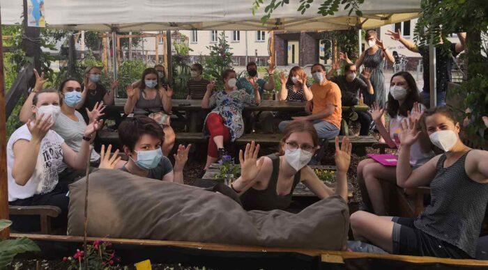 Eine Gruppe von Menschen, die an Tischen sitzen und die Hände gehoben haben.